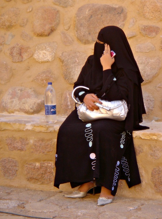 Woman in a burka and high heels, bag and mobile phone